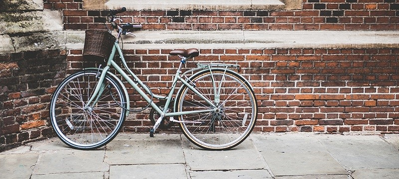 Photo of a bike leaning against a brick wall in Cambridge.
