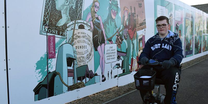 Photo of Gordon beside street art.