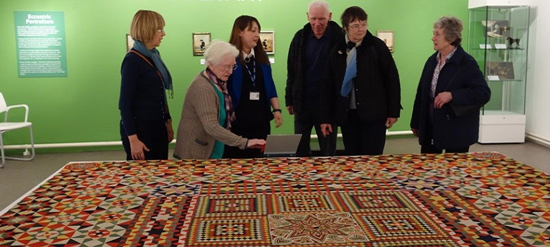 Photo of people looking at a rug in the gallery.