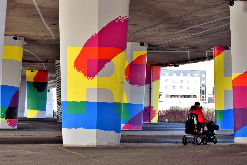 Photo of a powerchair user viewing street art in Dundee.
