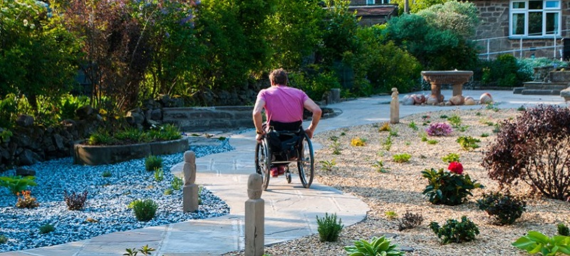 Photo of a wheelchair user exploring the garden.
