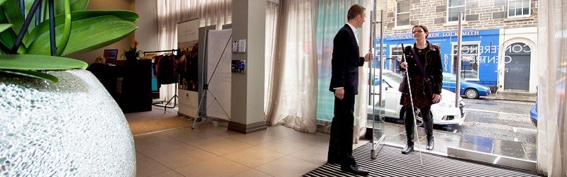 Photo of a hotel staff member meeting a long cane user at the front entrance.