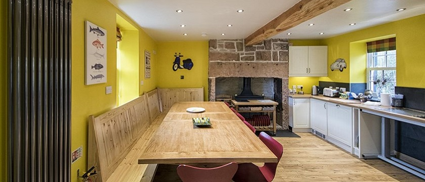 Photo of a yellow kitchen with large wooden table in The Moat House.