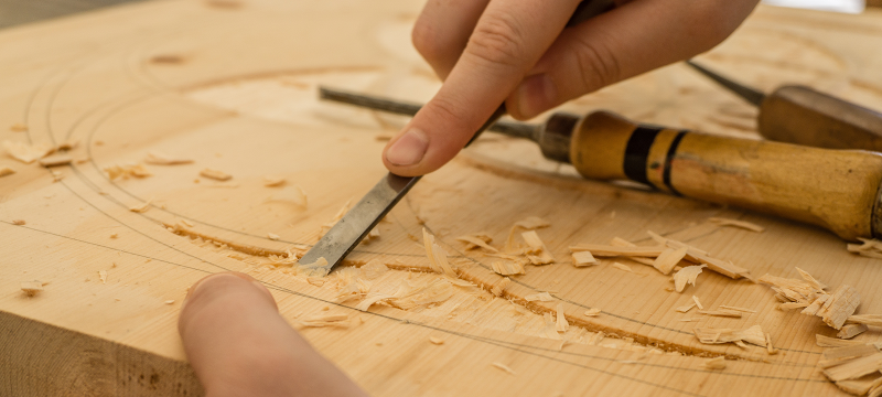 Photo of hands carving a piece of wood.