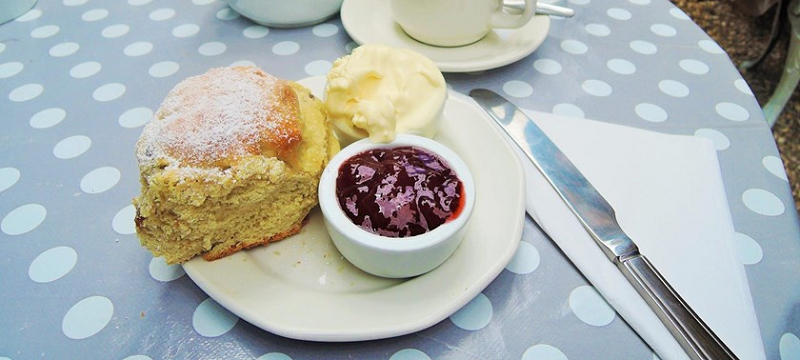 Photo of a scone with clotted cream and jam.