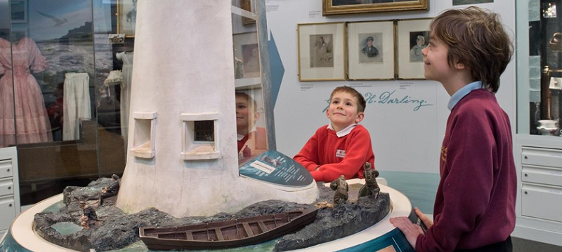 Photo of two children at the RNLI Grace Darling Museum admiring a lighthouse miniature display.
