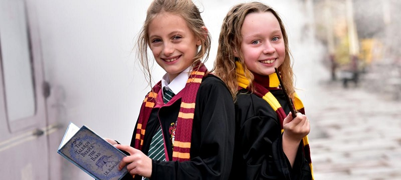 Photo of two girls dressed with Harry Potter costumes and holding a JK Rowling book.