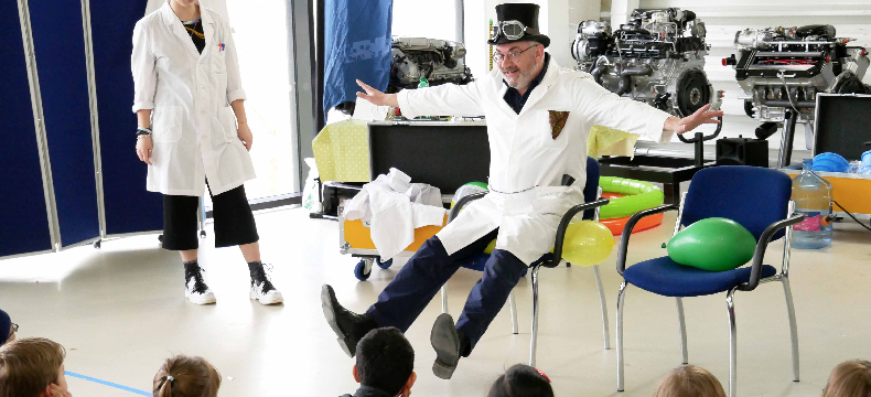 Photo of two actors dressed as scientists impressing an audience of children seating on the ground.
