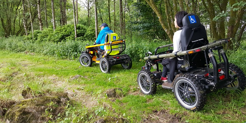 Photo of a man and a woman ridding all-terrain vehicles through a hiking path surrounded by forest.