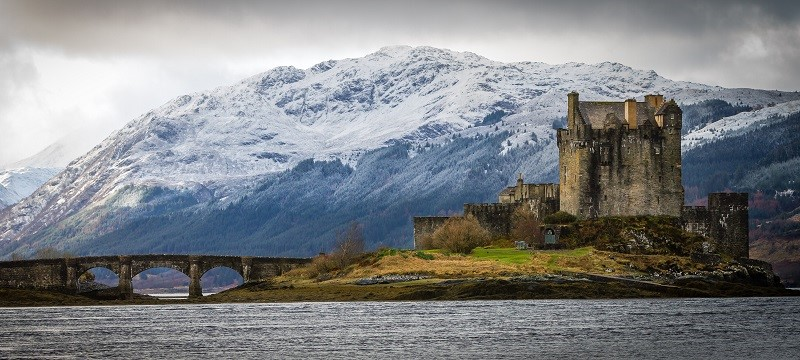 Photo of Eilean Donan Castle with mountains on the background and surrounded by a lake.