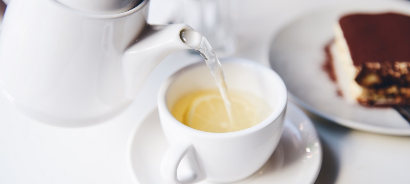 Photo of tea pot pouring hot water in a tea cup with slices of lemon.
