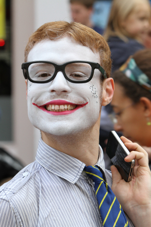 A photo of a man with a painted face holding a mobile phone.