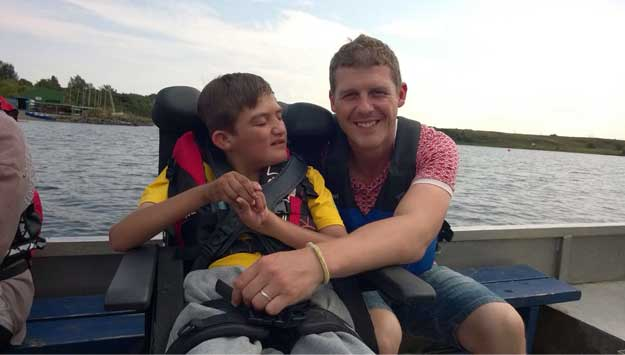A photo of a man hugging a boy on a boat.