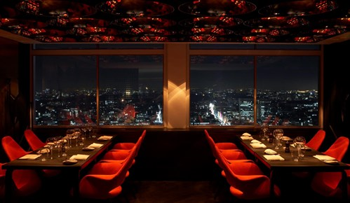 Photo of an empty restaurant looking out over a city.