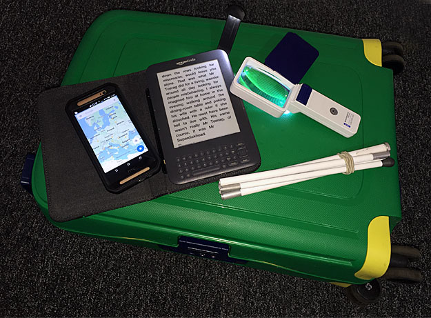 A photo of a magnifier, symbol cane, a Kindle and a mobile phone.