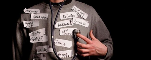Photo of a man holding a stethoscope to his jumper which is covered in sticky labels with words written on them.