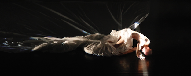 Photo of Marc Brew dancing with white sheets against a black backdrop.