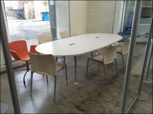 Photo showing white meeting table and chairs on ground floor.
