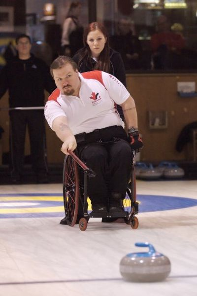 A photo of a man curling from his wheelchair.