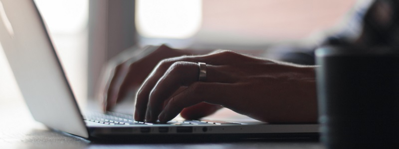 Photo of a person typing on a laptop.