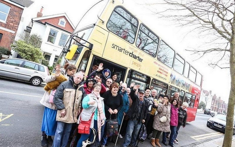 Photo of a bus and a group of people.