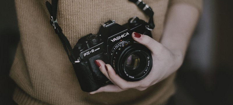 Photo of a girl holding a camera.